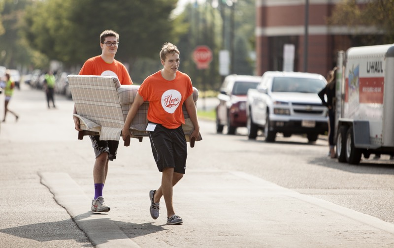 Student assistants carry a couch down the street on Move-In Day