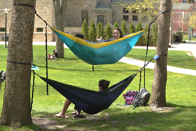 Hope College students laying in hammocks, one hammock installed above the other