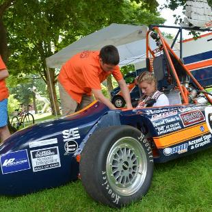 A member of Hope Motorsports helps a student test drive during the Activities Fair