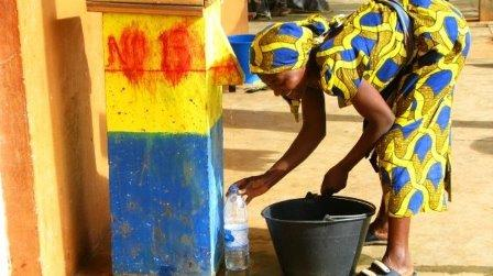 Woman getting water from well in Cameroon.