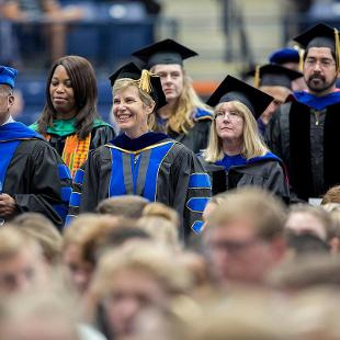 Faculty in academic regalia watch as the new students arrive for Convocation held at the DeVos Fieldhouse.