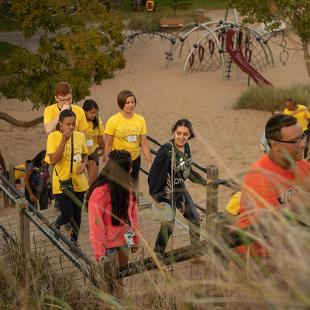 A group of students  participating in Step2Success pre-orientation program spend time at Tunnel Park Beach and are climbing the sand dune steps on their way to see Lake Mihicgan.