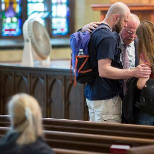 President Dennis Voskuil and Betty Voskuil pray together with two student in Dimnent Memorial Chapel.