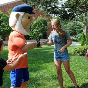 Hope's mascot Dutch greets several female students returning to campus.
