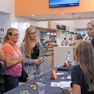 Student volunteers talk with a new student and her parents at the Orientation Station in the Jim and Martie Bultman Student Center.
