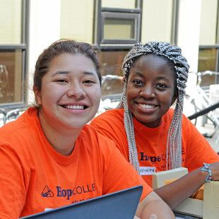 Two female students are ready to check in new students into the residence hall.