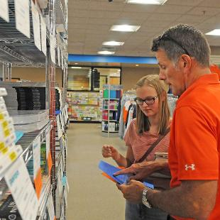 A family shops for books for class at the Bookstore during Orientation weekend.