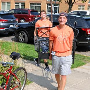 Two student Orientation volunteers help carry belonging into the residence halls.
