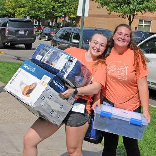 Two female Orientation volunteers help carry belonging into the residence halls.