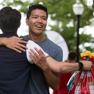 Two male students greet each other with a hug during the Activities Fair.