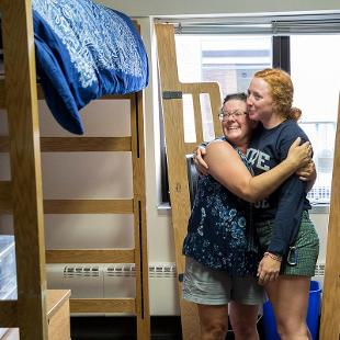 A student moving into her residence hall is hugged by her mother.