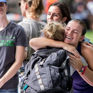 Two female students greet each other with a hug during the Activities Fair.