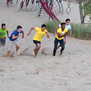 Six male students race up the dunes at Tunnel Park.