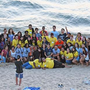 A group photo of students  participating in Step2Success pre-orientation program on the beach at Tunnel Park on Lake Michigan.
