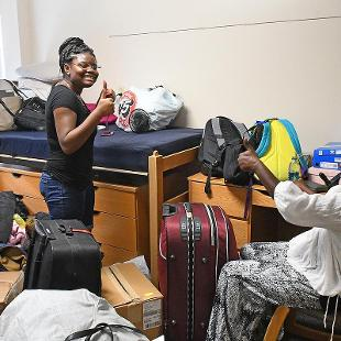 A student move into her residence hall with the help of her mother.