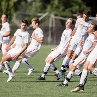 Action shot of part of the Men's Soccer team running warm-up drills in their uniforms, which are all white with orange stripe.
