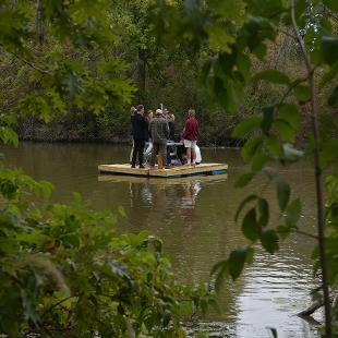 A raft with alumni of the Knickerbocker fraternity floats near the pull site in the Black River
