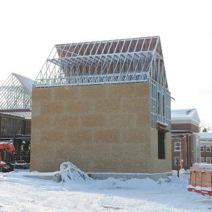 Exterior plywood walls help keep workers warm during winter construction as well as future define the building's shape.