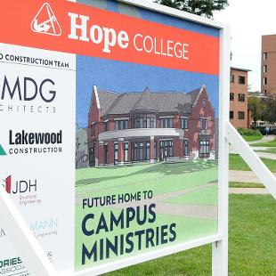 A sign shows the architect's drawing of what the new Campus Ministries house will look like when completed.