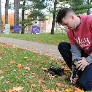 A male student helps set up lights to illuminate the area in the Pine Grove once the sun sets.