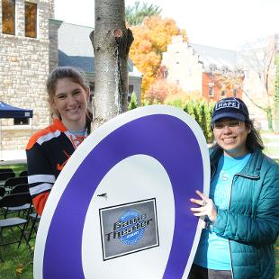 Two female students help set up a game area for participants on the Relay for Life event.