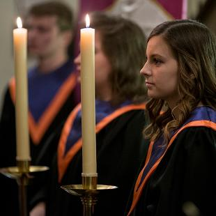 Two College Chorus members carrying candles are part of the processional.