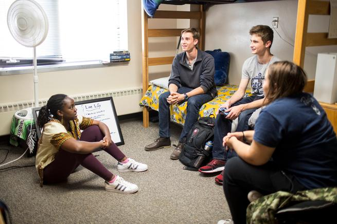 Four students hanging out in Scott Hall dorm room.
