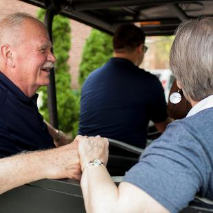 Dennis and Betty Voskuil riding together in the back of a campus golf cart during Orientation Weekend.