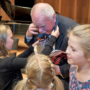 Dennis Voskuil with granddaughters admiring his Presidential Medallion
