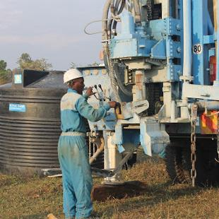Man working on air rotary drill rig