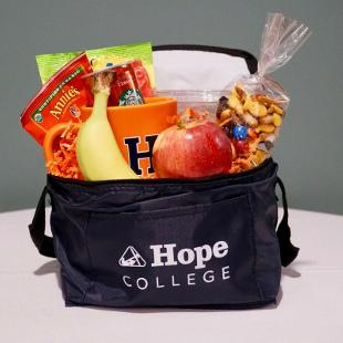 A reusable Hope College lunch bag stuffed with 1 Starbucks Espresso Double Shot, Yogurt covered pretzels, Annie's Cheddar Crackers, House Trail Mix, Sour Patch Kids, and 2 pieces of whole fruit.