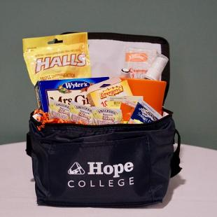 A reusable Hope College lunch bag stuffed with a Hope College Mug, herbal tea, Smucker's honey, Chapstick, Halls cough drops, Emergen C, hand sanitizer, and Mrs. Grass instant soup.