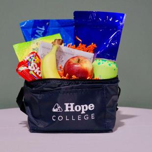 A reusable Hope College lunch bag stuffed with tasty vegan snacks! Sour Patch Kids, Skittles, Quinn Microwave Popcorn, Chex Mix, House Hummus with Carrots, 2 pieces of whole fruit, and 1 can of Bubly.