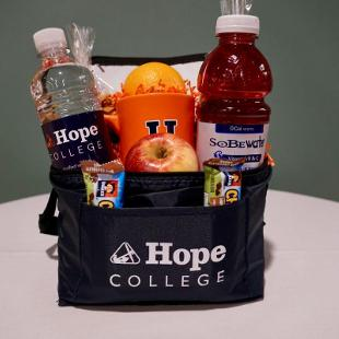 A reusable Hope College lunch bag stuffed with a Hope Mug, House Trail Mix, Dutch Braids, 2 Quaker Chocolate Chunk Whole Grain Low Fat Granola Bars, Hope labelled water bottle, Sobe Lifewater, and 2 pieces of whole fruit