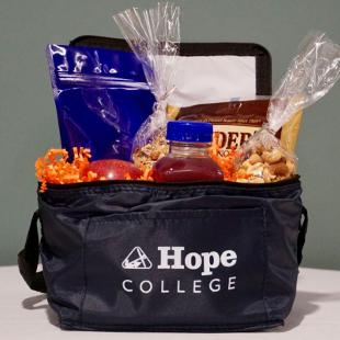 A reusable Hope College lunch bag stuffed with Naked Juice, house-made granola, Yoplait Light yogurt, carrots and hummus, Snyder's mini pretzels, hand fruit, and mixed nuts.