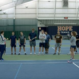 A large group of Hope students receiving tennis instruction