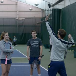 A male and female student receive tennis instructions