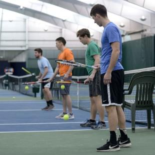 Male Hope students practicing tennis