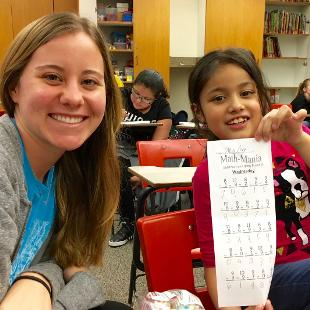 A CASA student smiling while holding a math worksheet with her mentor