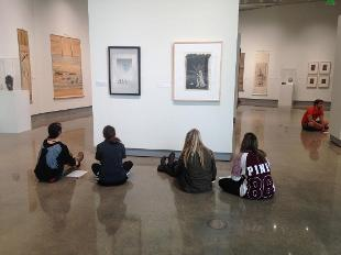 Hope College students studying artworks while seated on the floor of the Kruizenga Art Museum's gallery space.