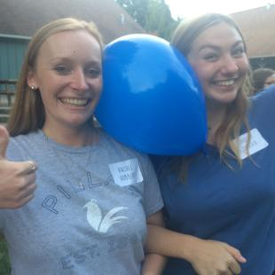 Two women laughing with a balloon on their shoulders
