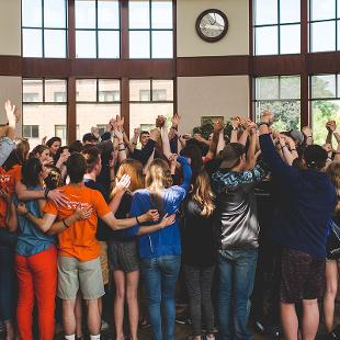 A group of Awakening students with their arms raised