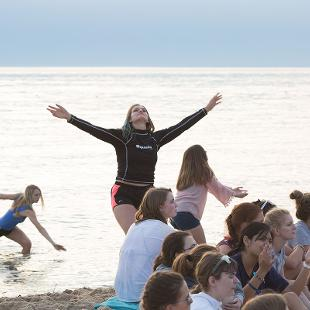 Students dancing on the beach and in the water