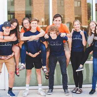 A group of students posing for a photo in piggy-back