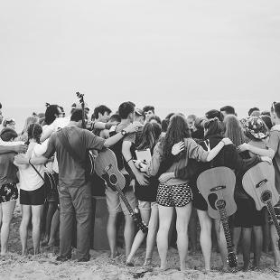 A group of students praying on the beach