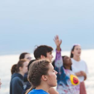 Students worshiping on the beach