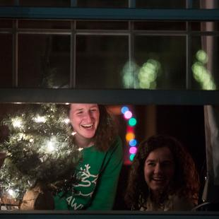 Student look down on the Christmas Tree Lighting from their residence hall.