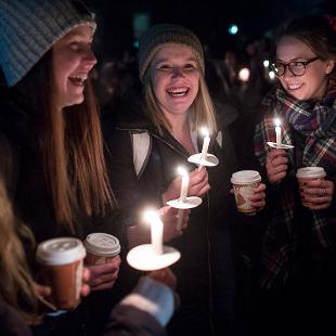 College students light hand-held candles prior to the annual Christmas Tree Lighting.