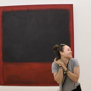 A student smiling in front of a large red and black painting