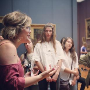 Students listening to a professor talk inside of an art museum